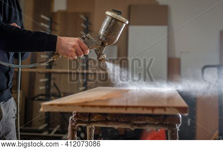 Professional Carpenter Varnishing The Wood For A Modern Furniture, Joinery And Woodwork Concept