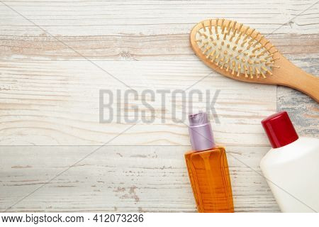 Hair Oil, Shampoo And Hairbrush On Light Background. Hair Care. Top View