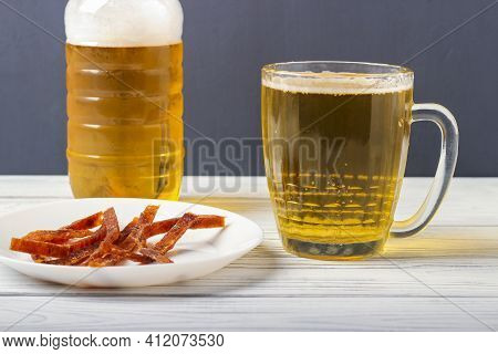 Beer In A Mug On The Table And Slices Of Dried Salted Fish On A Platter
