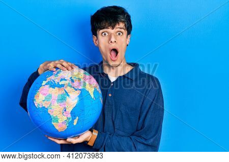 Handsome hipster young man holding world ball afraid and shocked with surprise and amazed expression, fear and excited face.