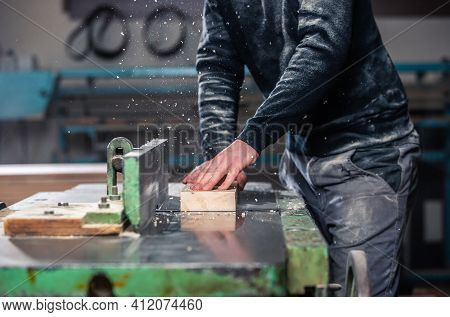 Professional Carpenter Milling The Wood On The Huge Saw For A Modern Furniture, Joinery And Woodwork