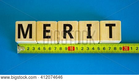 Merit Symbol. Wooden Cubes With The Word 'merit'. Beautiful Blue Background, Copy Space. Yellow Rule