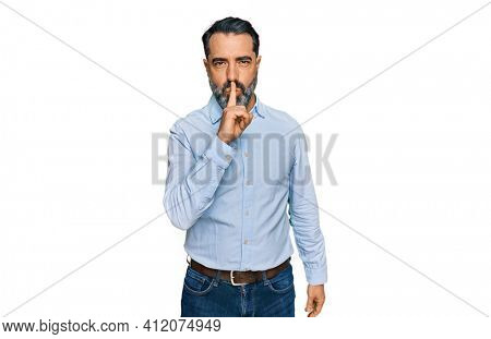 Middle aged man with beard wearing business shirt asking to be quiet with finger on lips. silence and secret concept.