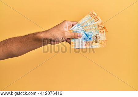 Hand of hispanic man holding swiss 10 franc banknotes over isolated yellow background.