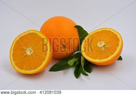 Healthy Ripe Delicious Fruits For Human Health. Juicy Fruits Of Orange Orange With Bright Green Mint
