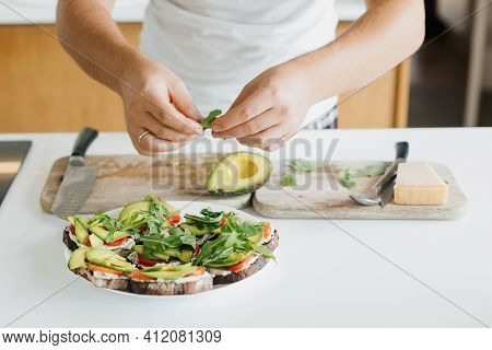 Young Man Making Toasts With Avocado, Tomato, Arugula, Cheese In Modern Kitchen. Home Cooking