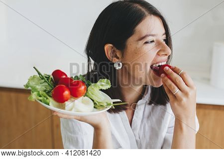 Healthy Eating And Home Cooking Concept. Young Happy Woman Eating Cherry Tomato And  Holding Plate W