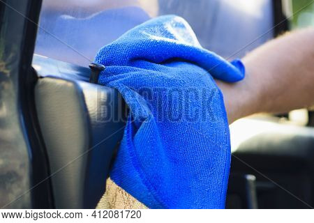 Hand Holding Blue Microfiber Cloth For Cleaning Dust On Black Car. Car Wash, Cleaning, Disinfection.