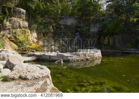Autumn Landscape Forest Stone Mountain Waterfall And Lake. A Picturesque Cascade Waterfall Among Lar