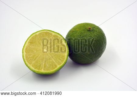 Healthy Ripe Delicious Fruits For Human Health. Juicy Fruits Of Green Sour Lime. One Half Of A Cut L