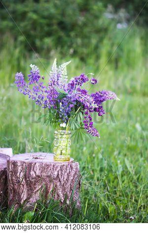 Bouquet Of Summer Flowers On Tree Stump. Large-leaved Or Bigleaf Lupine Purple Flowers. Lupinus Poly