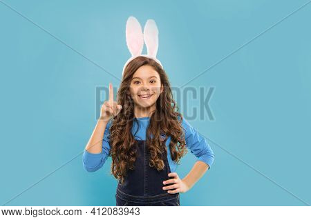 Happy Easter Idea. Little Child Got Idea. Small Girl Point Finger Up Blue Background. Idea To Celebr
