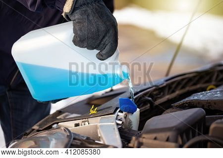 Man Filling Antifreeze Coolant For Cleaning Front Window With Snow In Background