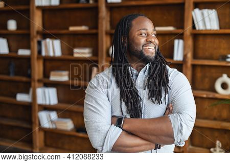 Smiling African Office Employee With Dreadlocks In Smart Casual Wear Stands With Arms Crossed In Con