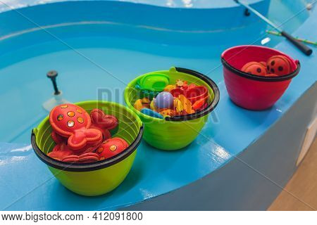 Fishing In The Paddling Pool. Childrens Toys In The Pool. Toy Fish Fishing Rod. Cheerful Children Fi