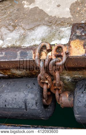 An Old Rusty Chain Connecting The Rubber Pipe Bumpers On The Sea Pier. A Fragment Of The Pier.