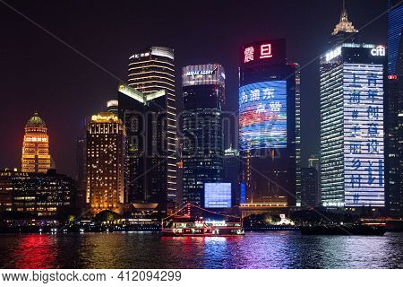 Night Cityscape Of Shanghai View From Bund Waitan Waterfront. Red Neon Lights Of Tourist Ship At Riv