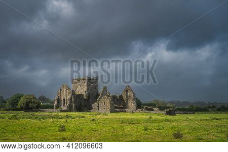 Old Ruins Of Hore Abbey Illuminated By Sunlight With Dark Dramatic Storm Sky. Located Next To Rock O
