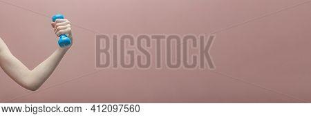 Boy's Hand Holding A Dumbbell On A Pink Background.children's Sport, Weak Athlete, Beginner Athlete.