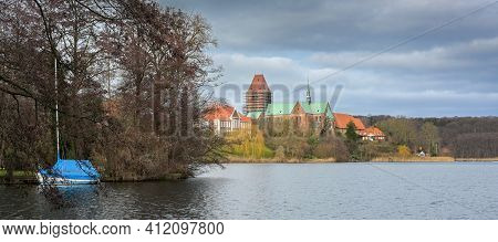 Lake Of Ratzeburg With Blue Boat And Cathedral (ratzeburger Dom) With Construction Scaffolding At Th