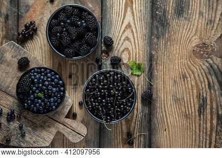 Blueberry, Blackberry, Blackcurrant In Bowls On A Wooden Background. Flat Lay, Top View, Copy Space.