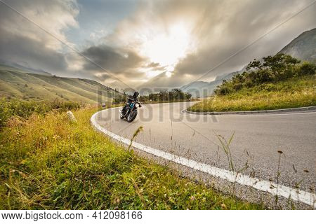 Motorcycle driver riding on mountain highway, Dolomites, central Europe.