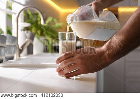 Man Pouring Milk From Gallon Bottle Into Glass At White Countertop In Kitchen, Closeup