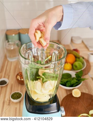 Woman Preparing Morning Breakfast For Vegan, Throws Spinach And Bananas To Blender Bowl For Detox Sm