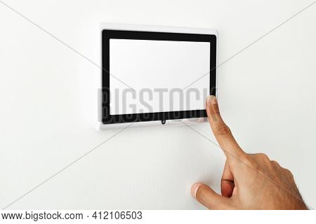 Finger pressing on smart home automation panel monitor