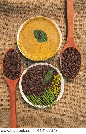 Top View Of Black Mustard Seed In Plate And Wooden Ladles With Mustard Sauce, Pods And Flower Isolat