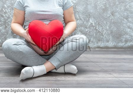 Pregnancy, Motherhood, People, Love And Expectation Concept - Close-up Of A Pregnant Woman Holding A