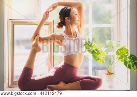Asian Woman Exercise At Home By Yoga In King Pigeon Pose Action.