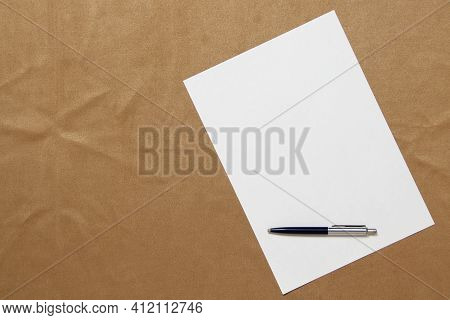 Template Of White Paper With Pen Lies Diagonally On Light Brown Cloth Background. Concept Of Busines