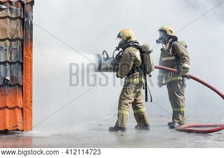 Firefighters Extinguishing Fire From Fire Hose, Using Firefighting Water-foam Barrel With Air-mechan