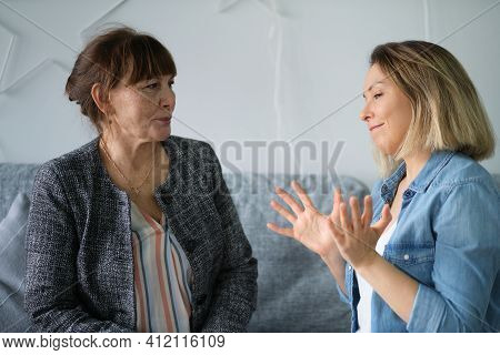Adult Daughter Talking To His Elderly Mom. Mother And Daughter Having Fun Enjoying Talk Sit On Sofa