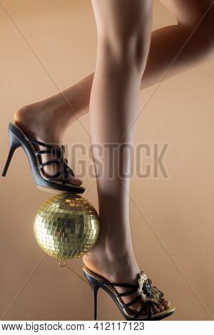 Celebrate Concept. Disco Ball On High Heels. Party Legs. Disco Event. Woman Heels With Gold Disco Ba