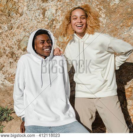 Happy couple in simple hoodies for winter outdoor shoot
