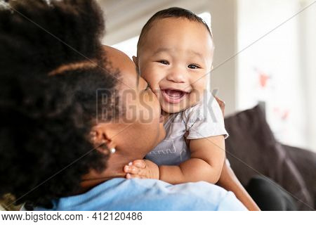 Happy African American mother kissing her son