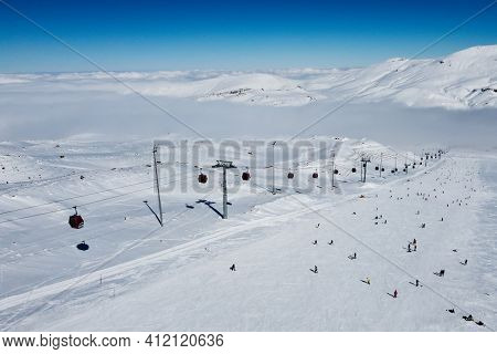 Gondola Type Cable Car And Skiers On Snow Covered Slope Of Ski Resort. Landscape With Snowy Ski Pist