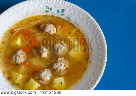 Soup With Meatballs In A White Ceramic Plate On Blue. Ready-to-eat Soup. Meatballs, Potatoes, Carrot