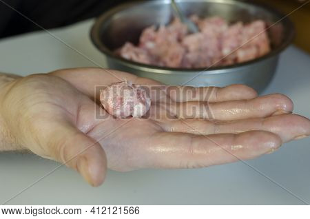 Male Hands Are Making Meatballs. A Middle-aged Man Makes Meatballs From Raw Minced Meat With His Han