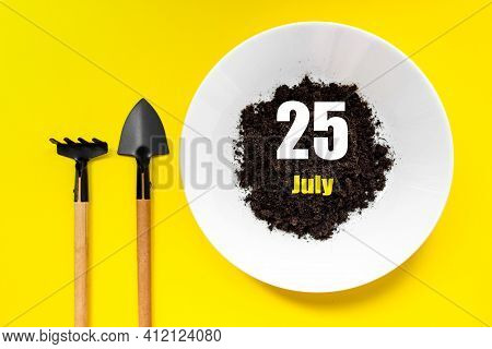 July 25th. Day 25 Of Month, Calendar Date. White Plate Of Soil With A Small Spatula And Rake On Yell