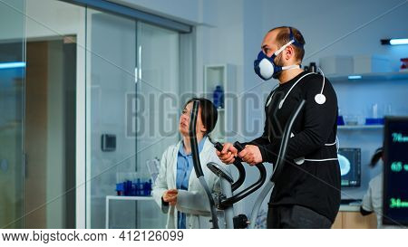 Medical Researcher Talking With Sportsman And Showing Ekg Scan On Virtual Screen While Measuring His