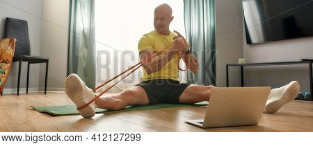Coach Pulling On A Sporting Elastic While Sitting At Home On A Sports Mat. Trainer 48 Years Old In S