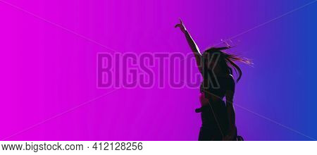 Silhouette Of Young Female Guitarist Isolated On Gradient Background In Neon.