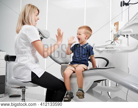 Happy Kid At Dentist Office Giving High Five To A Dentist