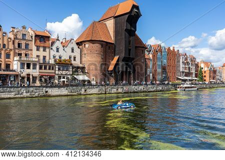 Gdansk, Poland - Sept 6, 2020: The Largest Medieval Port Crane In Europe And Historic Buildings On T