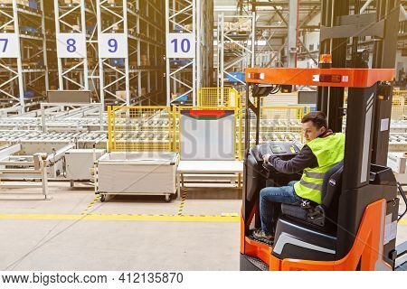 Storehouse Employee In Uniform Working On Forklift In Modern Automatic Warehouse. Boxes Are On The S