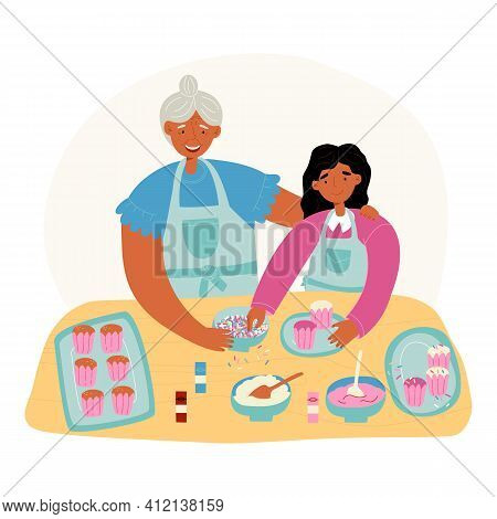 Family Pastime. Granddaughter Helps Her Granny With Cupcakes Baking And Decorating With Icing And To