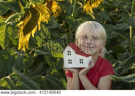 Blond Boy With Small House In Hands. Field Of Sunflowers. Eco-friendly Home. Green Houses